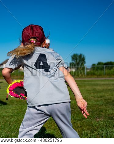 Blonde Caucasian Girl With A Hat Throwing A Baseball