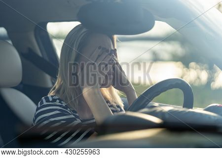 Stressed Woman Crying In Car. Middle Age Female Driver Feeling Headache Or Stress Hiding Face In Han