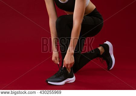 Woman Tying Shoelaces In Sportswear On A Red Background.