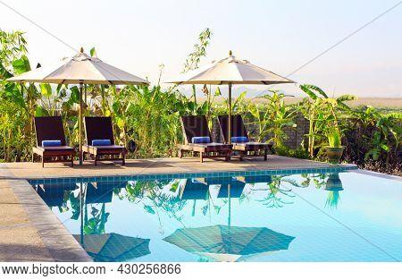 Sunbeds beside swimming pool. Umbrellas, lounge chairs and pool, Myanmar