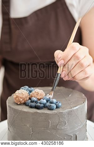 Woman Pastry Chef Decorates Grey Cake With Blueberries And Glitter, Close-up. Cake Making Process, S