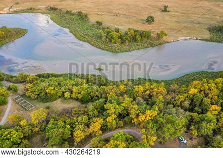 shallow and wide Dismal River flowing through Nebraska Sandhills at Whitetail Campground in Nebraska National Forest, aerial view of afternoon scenery in early fall