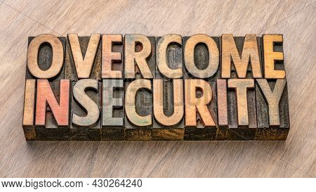 overcome insecurity word in vintage letterpress wood type, confidence and personal development concept