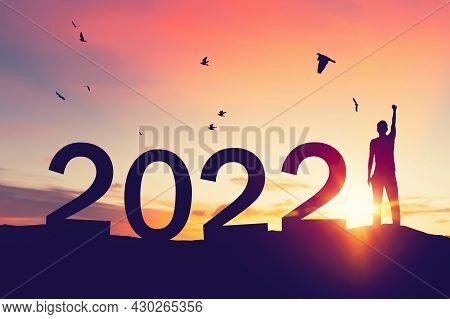Man Raise Hand Up On Sunset Sky With Birds Flying At Top Of Mountain And Number Like 2022 Abstract B