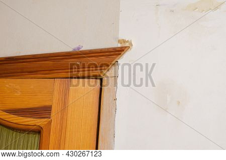 A Wall With Remnants Of Paper Wallpaper. Vertical Wall Of The Living Room. Fragment Of Wooden Door F