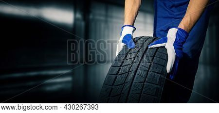 Car Tire Shop And Service - Mechanic Holding New Tyre On Garage Background. Copy Space