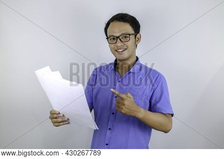 Young Asian Man Is Smile And Happy When Looking On Paper Document. Indonesian Man Wearing Blue Shirt