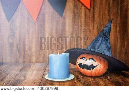 Halloween Pumpkin And Candle On Wooden Background In Moonlight