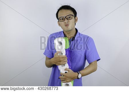Asian Man Is Mad And Angry When Shopping Bag With Tissue Toilet Paper Rolls. Buying Panic For Home Q