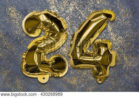 The Number Of The Balloon Made Of Golden Foil, The Number Twenty-four On A Gray Background With Sequ