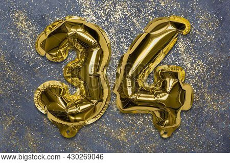 The Number Of The Balloon Made Of Golden Foil, The Number Thirty-four On A Gray Background With Sequ