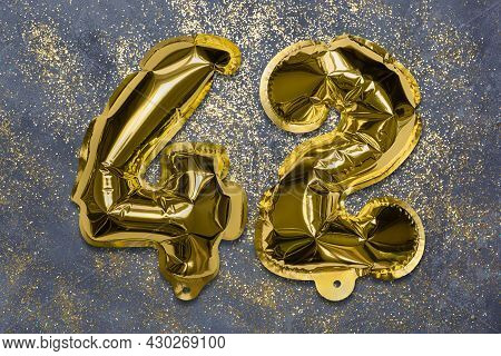 The Number Of The Balloon Made Of Golden Foil, The Number Forty-two On A Gray Background With Sequin