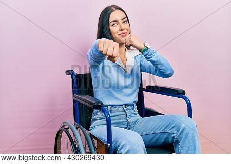 Beautiful woman with blue eyes sitting on wheelchair punching fist to fight, aggressive and angry attack, threat and violence