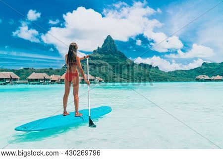 SUP Tahiti paddleboard woman standing on stand-up board paddling over turquoise ocean at luxury beach resort hotel on Bora Bora island, French Polynesia.