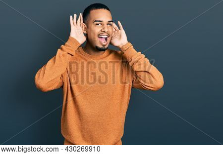 Young african american man wearing casual clothes smiling cheerful playing peek a boo with hands showing face. surprised and exited
