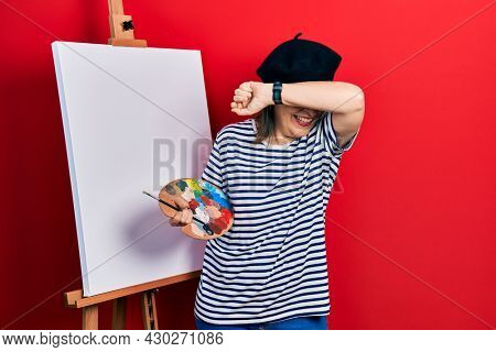 Middle age hispanic woman standing drawing with palette by painter easel stand smiling cheerful playing peek a boo with hands showing face. surprised and exited