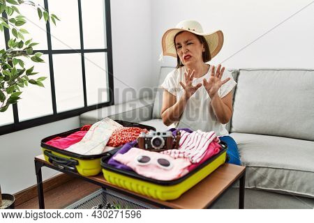 Beautiful middle age hispanic woman packing summer clothes in suitcase disgusted expression, displeased and fearful doing disgust face because aversion reaction. with hands raised