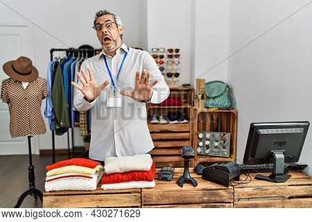 Middle age hispanic man working as manager at retail boutique afraid and terrified with fear expression stop gesture with hands, shouting in shock. panic concept.