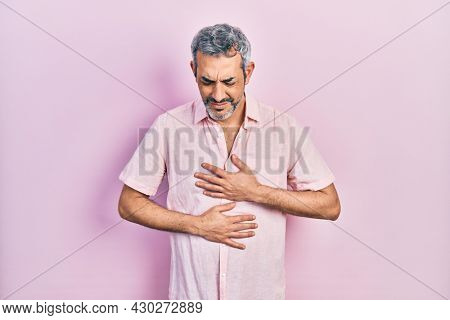 Handsome middle age man with grey hair wearing casual shirt with hand on stomach because indigestion, painful illness feeling unwell. ache concept.