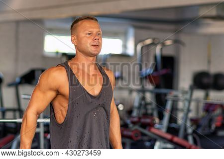 Fitness Man Warming Up In Gym. Male Doing Warm Up Stretching Workout On Gym Background.portrait Of A