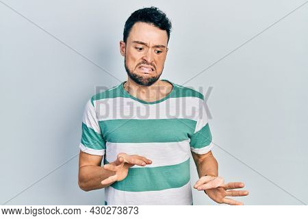 Young hispanic man wearing casual clothes disgusted expression, displeased and fearful doing disgust face because aversion reaction.