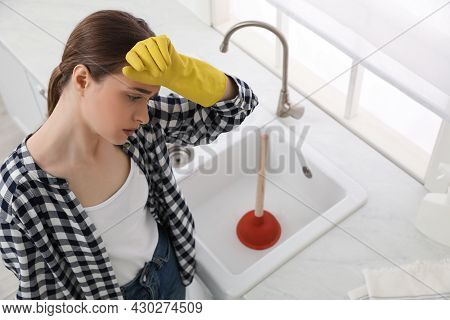 Tired Young Woman Near Clogged Sink With Plunger In Kitchen, Above View
