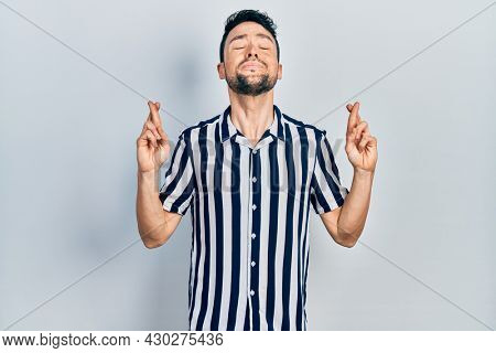 Young hispanic man wearing casual clothes gesturing finger crossed smiling with hope and eyes closed. luck and superstitious concept.