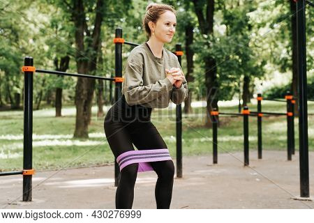 Strength Training On Open Sports Ground. Fit Young Woman In Sportswear Doing Squats With Elastic Ban