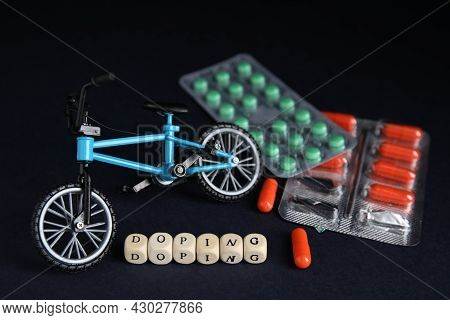 Word Doping, Pills And Bicycle Model On Black Background
