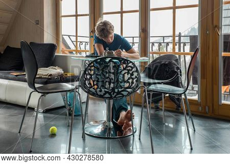 Pensive young man sitting at table drink coffee work at notebook thinking of problem solution, thoughtful male employee pondering considering idea writing at paper. Education at home.
