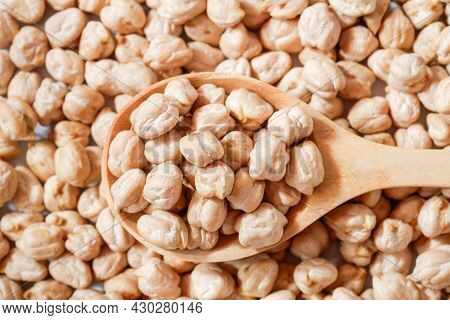Close-up Chickpeas In A Wooden Spoon On A Pile Of Chickpeas , Top View, Is A Healthy Nut That Is Per