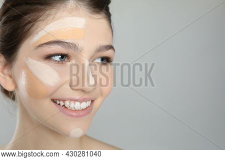 Beautiful Girl On Grey Background, Closeup. Using Concealer And Foundation For Face Contouring