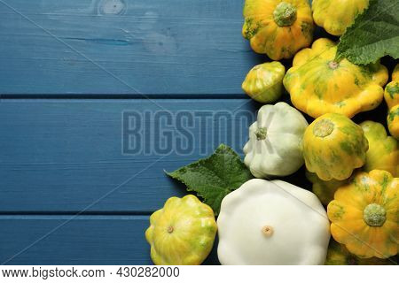 Fresh Ripe Pattypan Squashes With Leaves On Blue Wooden Table, Flat Lay. Space For Text