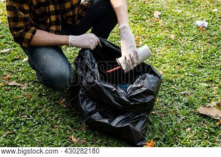 Man's Hands Pick Up Plastic Bottles, Put Garbage In Black Garbage Bags To Clean Up At Parks, Avoid P