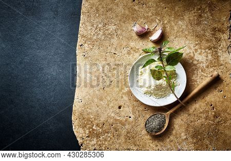 Grated Parmesan, basil, garlic and black pepper on rustic stone background. Copy space