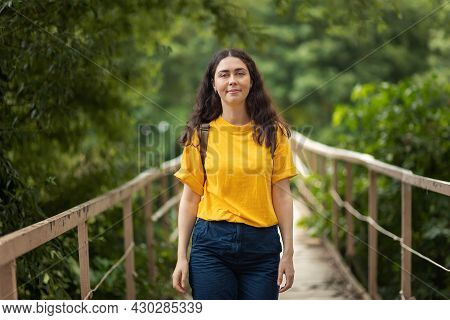 A Young Caucasian Woman Smiles While Standing On The Bridge. In The Background Is A Green Summer For