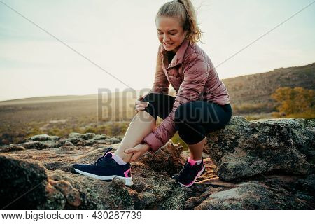 Caucasian Female Hiking On Mountain Holding Sprained Ankle In Pain Waiting For Help Sitting On Rock