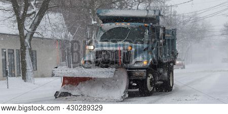 Babylon, New York, Usa - 1 February 2021: A Blue Municipal Snowplow Truck Is Clearing Main Street In