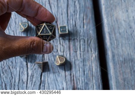 Person Of Color Holding A 20-sided Role-playing Die Between The Fingers. In The Background A Set Of