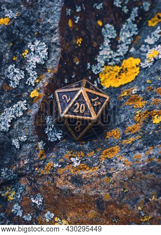 Vertical Image Of A 20-sided Metallic Role-playing Game Die On A Rocky Surface Covered With Lichen