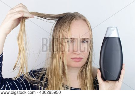 The Girl Looks In The Mirror At Her Oily Hair, Then Takes A Shampoo To Treat Oily Hair. Problematic
