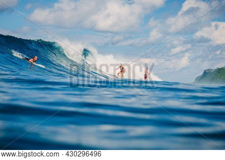 April 04, 2021. Bali, Indonesia. Sporty Young Woman With Surfers In Tropical Ocean During Surfing. S