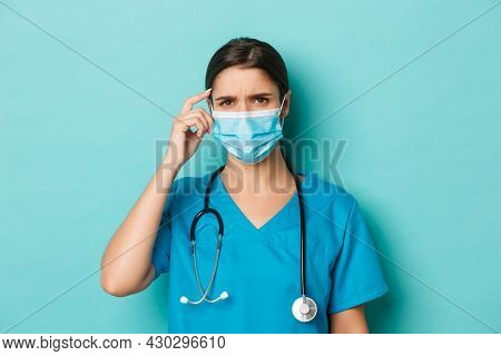 Concept Of Covid-19 And Quarantine Concept. Close-up Of Confused Female Doctor In Medical Mask And S
