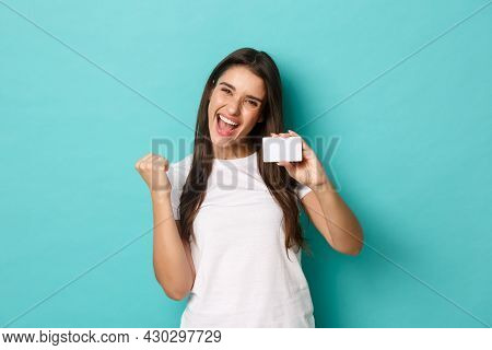 Image Of Satisfied Ecstatic Woman, Wearing White T-shirt, Rejoicing And Showing Credit Card, Standin