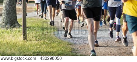 Legs Of A Large Group Of Runners Running A 5k Race On A Dirt Path Around Belmont Lake In North Babyl