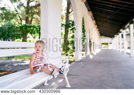Little Girl In A Dress Sits On A White Bench In A Pavilion In The Park