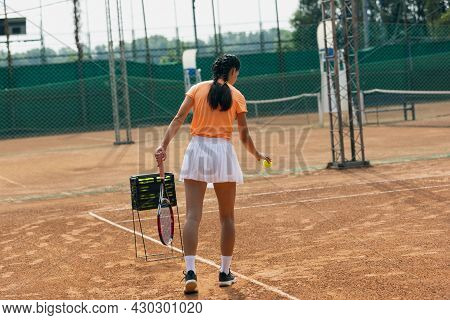 One Young Sportswoman, Professional Tennis Player With Racket Practicing On Clay Tennis Court In Sum