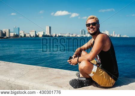 Attractive Adult Boy In Sunglasses And Stylish Shirt Sitting With Crossed Legs On Stone While Smilin