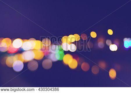 Beautiful Bokeh Of The Night City Lights. Blur Background Of Skyscraper Buildings. Unfocused Old Cit