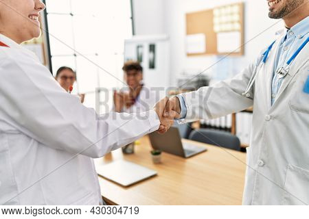 Group of doctor clapping to partners handshake in a medical meeting at the clinic office.
